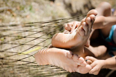 family tickle: Picture of man and little childs feet resting in hammock. Closeup of happy family tickling and having fun on sunny summer day background. Stock Photo