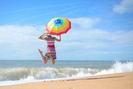 ladies: Picture of exciting beautiful young lady with rainbow umbrella jumping on sunny seashore. Backview of pretty lady having fun on blurred summer sky outdoor background.