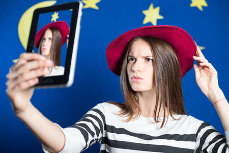 Portrait of beautiful young lady making selfie and correcting her hat. Pretty girl frowning and looking stressed on blue screen with stars indoor background.