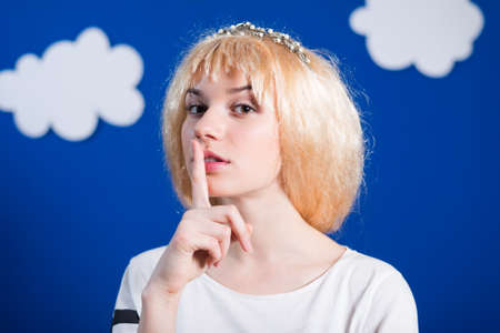 shushing: Portrait of beautiful young lady in golden wig shushing. Pretty girl looking at camera on dark blue with white paper clouds indoor background.