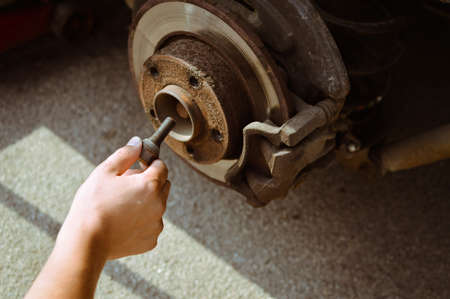 hand brake: Picture of man changing old wheel. Closeup of hand working with disk and brake block on blurred background. Stock Photo