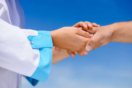 support: Picture of nurses hands holding someones hand with care. Closeup of medicine support on blue sky background.