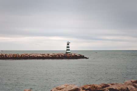 sombre: Picture of striped lighthouse on rocky pier in cold sea. Symbol of hope on sombre sky and grey water background.