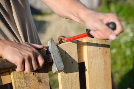 ウッド フェンス ゲートの修復の画像。バールとハンマーぼやけ夏屋外背景に男性の手のクローズ アップ。 写真素材