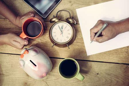 planificacion familiar: Cuadro de escritura de la mano del hombre y las manos celebración taza de café al lado hucha y despertador de la mujer. Vista superior de planificación familiar alguna de compra sobre fondo de madera tabla tablón.