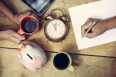 family planning: Picture of mans hand writing and womans hands holding cup of coffee beside piggy-bank and alarm-clock. Top view of  family planning some purchasing on wooden plank table background.