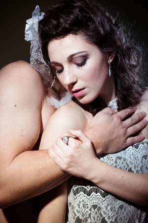 hat nude: Portrait of beautiful romantic couple with eyes closed hugging on light background Stock Photo