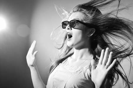 wind blown hair: Portrait of surprised young beautiful lady in 3d glasses looking amazed. Black and white photography
