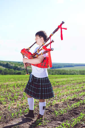 kilt: Picture of man enjoying playing pipes in Scottish traditional kilt on green outdoors copy space summer field background