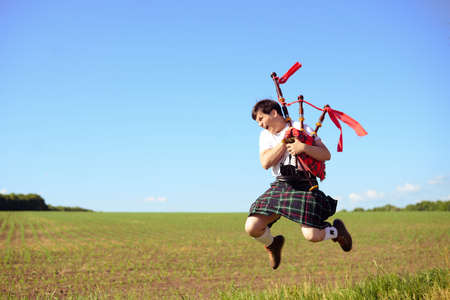 kilt: Portrait of man jumping high with pipes in Scottish traditional kilt on green outdoors copy space summer field