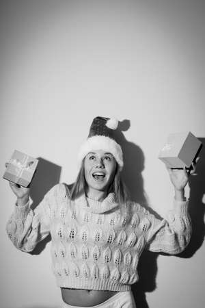 black and white photography: Portrait of exciting beautiful girl in Santa hat with gifts. Black and white photography Stock Photo