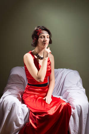shush: Elegant retro style beautiful woman in red dress showing hand silence sight as if to say hush and sitting in the chair