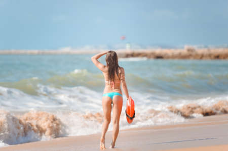 baywatch: Picture of beautiful young woman with orange lifesaver equipment on beach. Sexy girl in bikini on blurred seascape background.