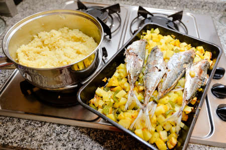cooktop: Picture of yellow cuscus in pot and four baked makrels with sweet potatoes. Tasty dinner on metal cooktop on kitchen indoor background.