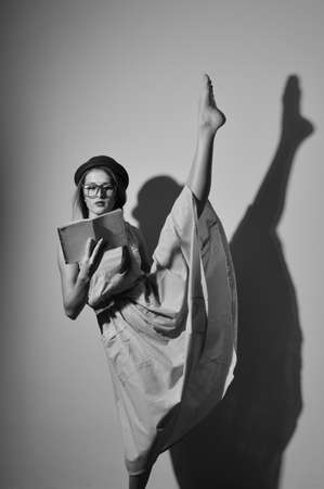 splitting up: Black and white photography of beautiful young lady ballet dancer. Elegant female in a bowler hat and glasses reading a book with legs split up in the air