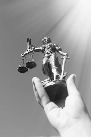 themis: Black and white photography of hand holding sculpture of themis, femida or justice goddess up in bright sky copyspace background Stock Photo