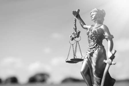 scales of justice: Black and white photography of sculpture of themis, femida or justice goddess on bright sky copy space background