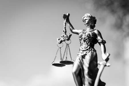 attorney scale: Black and white photography of sculpture of themis, femida or justice goddess on bright sky copy space background