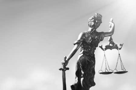 balanza de justicia: fotografía en blanco y negro de la parte posterior de la escultura de Themis, diosa Femida o la justicia en el cielo brillante fondo de copyspace