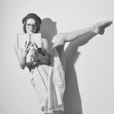 split up: Black and white photography of beautiful young lady ballet dancer. Elegant female in a bowler hat and glasses reading a book with legs split up in the air