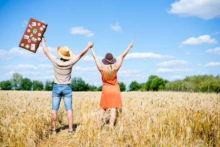 manos levantadas al cielo: Imagen de la feliz pareja levantó las manos en campo de trigo. Emocionado hombre joven y la mujer con la maleta que celebra éxito en el cielo azul de fondo de campo.