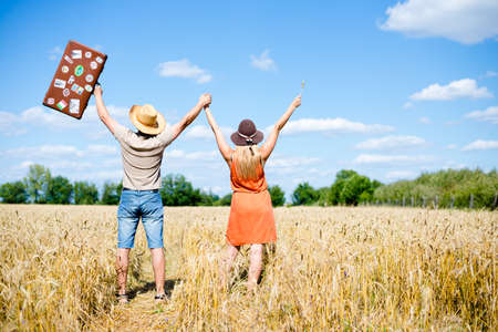 Picture of happy couple raised hands together in wheat field. Excited young man and woman with suitcase celebrating success on blue sky countryside background. Imagens