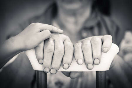 broken trust: Close up picture on senior and young person hands holding crutch. Black and white photography