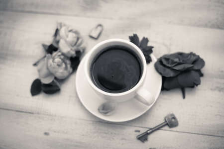 black and white lock: Black and white picture of cup of coffee and rose petals beside with lock and key as symbol of security Stock Photo