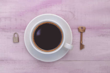 key to freedom: Closeup picture of cup of coffee with lock and key on both sides as symbol freedom