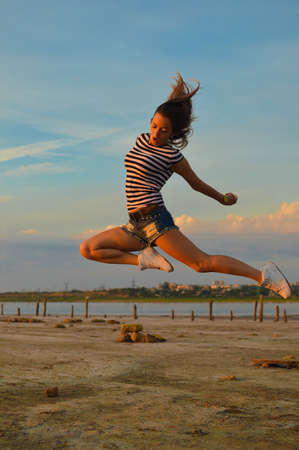 sea nymph: Picture of beautiful amazed young lady having fun jumping high over outdoors copy space background Stock Photo