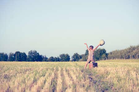 médula: Fotografía de un niño feliz con las manos levantadas en campo del país. Pequeño explorador con el sombrero de explorador y la maleta vieja en el fondo borrosa campo. Foto de archivo