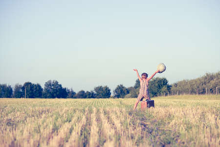 m�dula: Picture of happy boy with raised hands in country field. Little explorer with pith helmet and old suitcase on blurred countryside background.