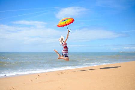 persona saltando: Imagen de la hermosa joven que sostiene el arco iris paraguas y saltando en la costa de oro. Backview de la muchacha bonita que se divierte en el cielo azul de fondo borroso al aire libre.