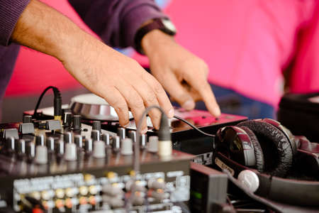 producer: Picture of producer adjusting volume with professional musical equipment and headphone. Closeup of male hands and equalizer on blurred pink indoor background.