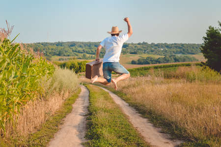 Picture of man in straw hat holding old valize and jumping on country road. Backview of excited traveller on blurred sunny outdoor background.