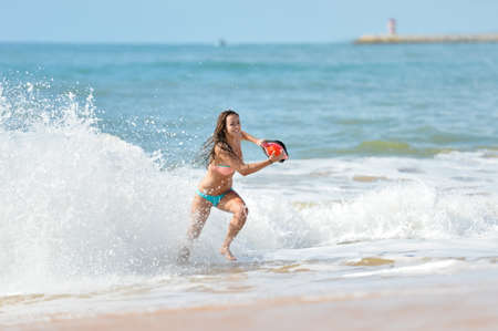 duty belt: Picture of beautiful young lady with orange lifesaver equipment in ocean waves. Sexy girl running on blurred seascape background.