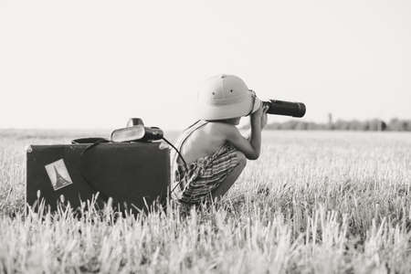 romper: Picture of boy wearing romper looking in spyglass in country field. Black and white image of little explorer with camerabag and old suitcase on blurred countryside background.