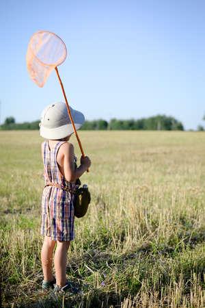 médula: Fotografía de un niño pequeño con el pie-red del insecto en el campo. Vista posterior del niño llevaba sombrero de explorador en la soleada fondo del campo de verano. Foto de archivo