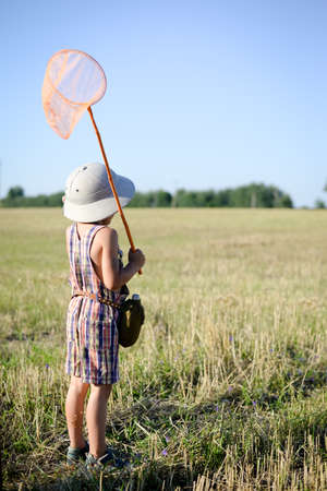 pith: Picture of little boy with insect-net standing on field. Back view of kid wearing pith helmet on sunny summer countryside background. Stock Photo