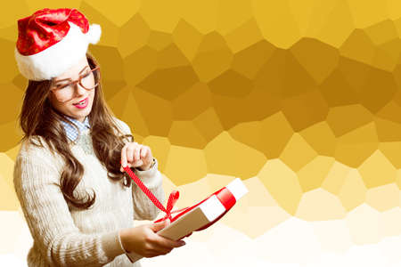 excited: Portrait of exciting beautiful young lady in Santa red hat and glasses opening gift box on festive abstract background