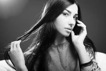 lady on phone: Portrait of pretty young lady talking on mobile phone and sensually looking at camera while touching luxury hair on copy space background. Black and white photography Stock Photo