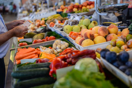 Picture of grocery stall with various fresh fruits and vegetables and man making purchases.