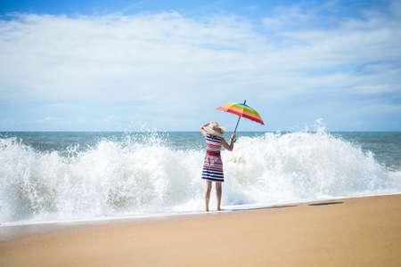 mujer mirando el horizonte: Foto de la dama de entrar en la onda espumosa y con paraguas de colores del arco iris mirando hacia fuera para algo en el fondo costa