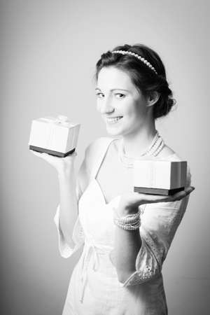 perls: Holding present boxes up beautiful young lady in elegant dress having fun happy smile on copy space background. Black and white photography