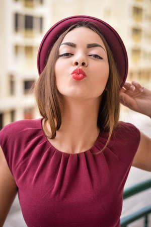 Closeup portrait of happy lady with red lips sending air kiss on modern building background Stock Photo