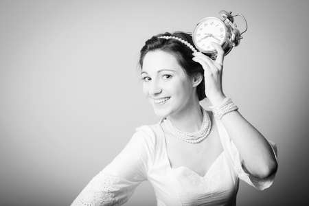perls: Black and white photography of elegant beautiful young lady having fun holding alarm clock up and happy smile on copy space background