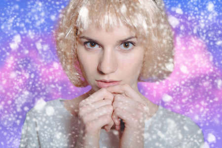 splotches: Photo of young female with chilling glance wearing white blonde wig on blue with purple splotches background Stock Photo