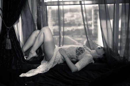 mujeres desnudas: Foto blanco y negro de la increíble mujer con un vestido transparente atractivo blanco y sujetador negro tumbado en alféizar de la ventana