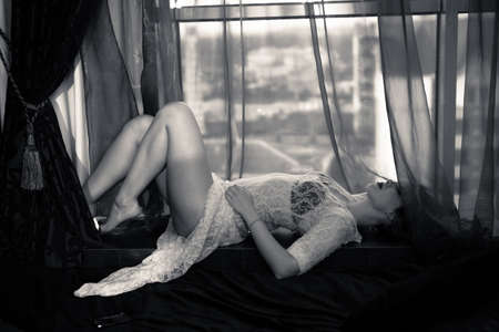 beautiful naked woman: Monochrome photo of amazing female wearing white sexy transparent dress and black bra lying on windowsill