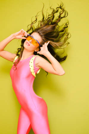 lycra: Portrait of sexy young curly brunette wearing pink lycra jumpsuit. Amazing female wearing big yellow safety glasses on studio light yellow background